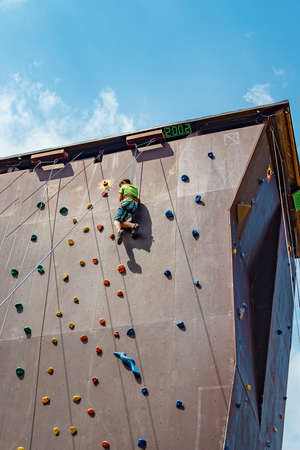A teenage boy is engaged in rock climbing