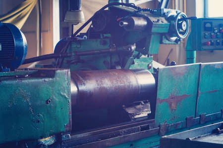 A large round piece is mounted on the machine and is ready for machining, grinding a large shaft on the machine