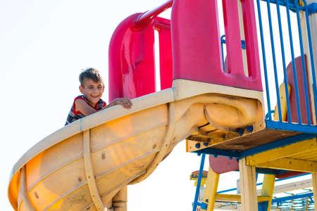 A happy and joyful boy descends on a childrens slide