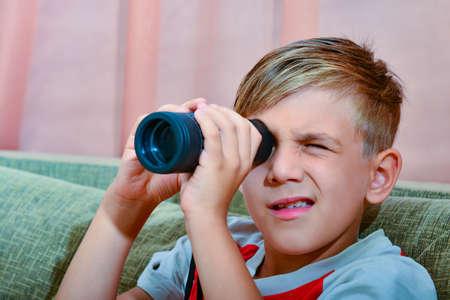 Le garçon regarde dans un monocle