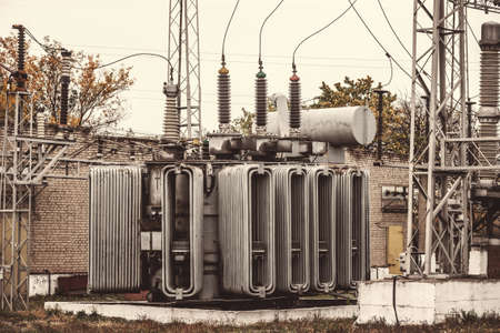 Transformer substation, high-voltage switchgear and equipment. Vintage photo of a power station with poles and wires Banque d'images