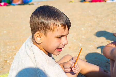 The boy covered himself with a towel after bathing and eats by the sea, on a sunny summer day Stock Photo