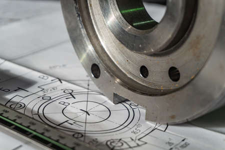 The transition flange after processing lies on the technical drawing. Next to the part is the measuring tool, a caliper Stock Photo