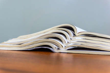Open magazines lie on top of each other on a brown table, documents are stacked close-up Banco de Imagens