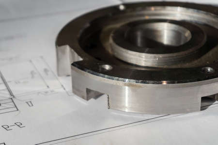 The transition flange after processing lies on the technical drawing. Detail ready to work with a drawing together in mechanical engineering Banque d'images