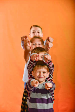 Four children stand in a row and point their fingers forward to the age on a yellow background, the younger ones look out for the older ones