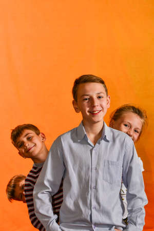 Four children stand in a row on a yellow background, the younger ones look out for the older ones