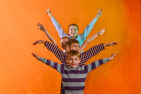 Four children stand in a row and raise their hands to the sides on the age of a yellow background, the younger ones look out for the older ones