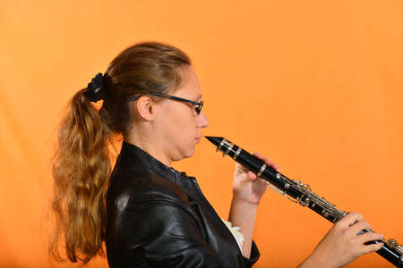 Girl in glasses in a black jacket plays the clarinet