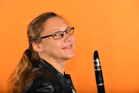 A girl with glasses in a black jacket holds a clarinet in her hands and looks into the camera, on a yellow background