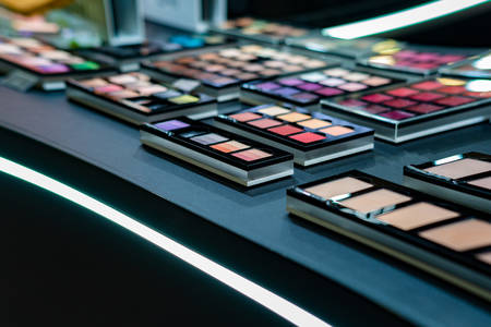 Cosmetics on the shop window with a variety of colors and shades, mascara, powder, paint for beauty and makeup. Consumerism, retail and purchase concept. Reklamní fotografie