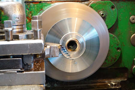 Machining of a round part on a lathe, facing by a worker on a mechanical feed. Chips fly in different directions. Stock Photo