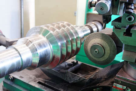 Grinding of the worm shaft on the backing machine. Industrial industry manufacturing gear shafts.