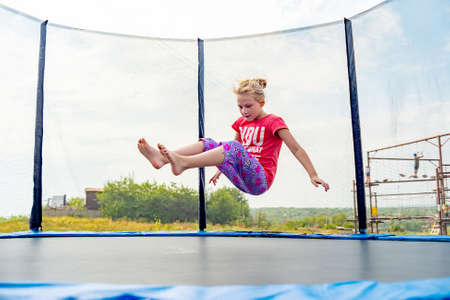 The girl falls on a rubber trampoline.
