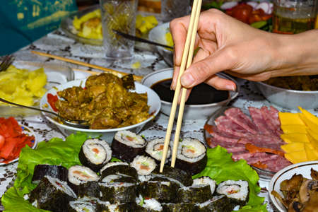 Female hand takes sushi with chopsticks, which lie on the green salad leaves.