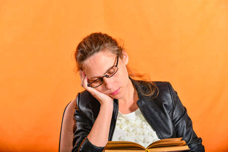 The girl in glasses with a book sits on a chair and falls asleep on an orange background. Tired of a lot of knowledge. 版權商用圖片
