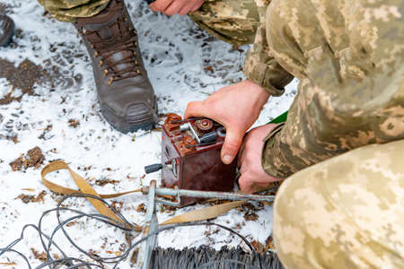Military soldiers explode a bomb with a detonator.