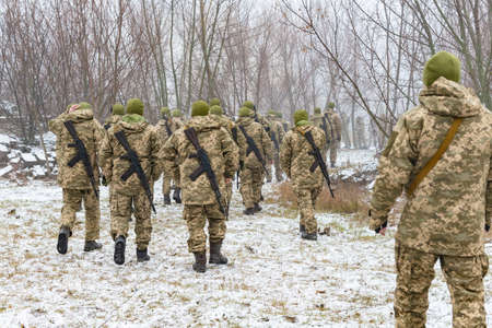 The military in camouflage with Kalashnikov assault rifles, behind their backs, go forward to attack the enemy in winter