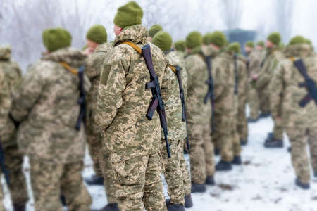 soldiers with  assault rifles stand in formation to prepare for battle and offensive. Editorial