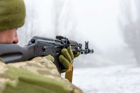 A military soldier takes aim with an automatic rifle and holds it in his mittens in winter.