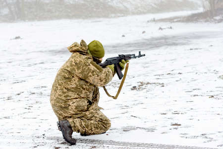 A combat soldier is aiming fire from a weapon, close-up.