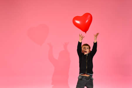 A boy throws and catches a heart-shaped balloon on a pink background in the studio. Stock fotó