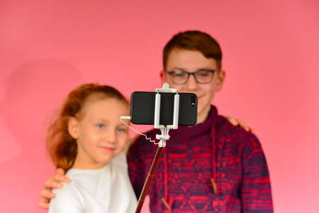Girl with a guy makes selfie in the studio on a smartphone, on a pink background.