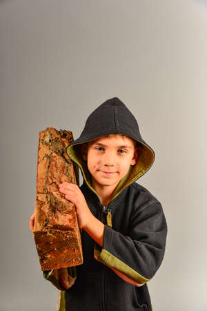 The boy holds a log on his shoulder, the guy carries firewood to light a fire