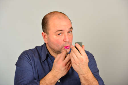 Glamorous and sexy adult man in a shirt, straightens makeup on his face, the concept of gender equality Foto de archivo