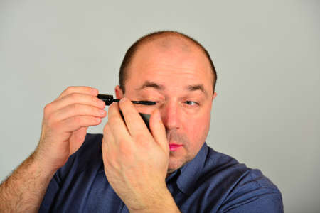 An adult man paints his eyelashes in front of a mirror, getting ready for a date