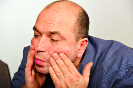 An adult and unshaven man in a blue shirt applies a mask of cream on his face, the concept of fashion, style and personal care