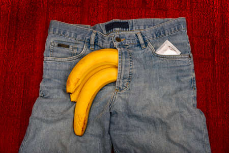 Imitation of an erect penis in jeans with a condom, protruding from the pants in the form of a yellow banana