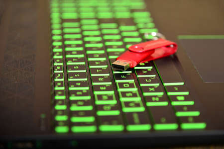 Red USB flash drive lies on the green laptop keyboard.