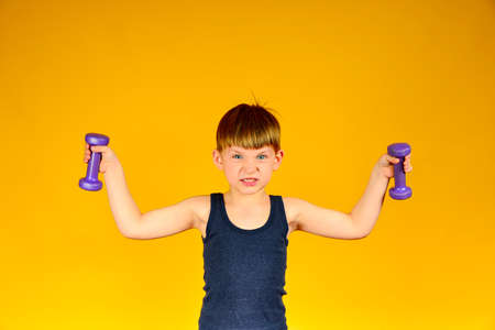 Mahi to the sides with dumbbells boy on a yellow background. Stockfoto