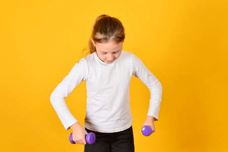 The girl is engaged in fitness with dumbbells, on a yellow background. 写真素材