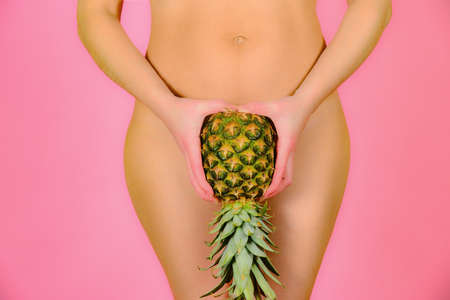 A young and sexy girl is holding a pineapple near the feet, on a pink background.