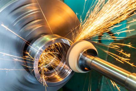 Endbearbeitung einer Metalloberfläche mit einem Schleifstein auf einer Rundschleifmaschine, Funken fliegen in verschiedene Richtungen