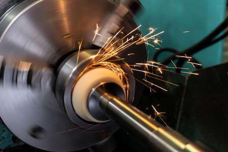 Innenbearbeitung des Lochs mit einem Schleifstein auf einer Schleifmaschine, Funken fliegen in verschiedene Richtungen Standard-Bild