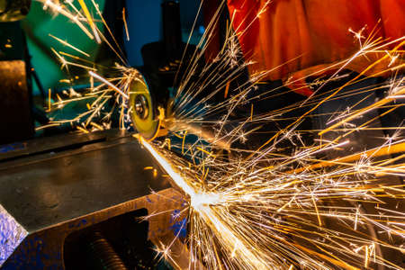 The worker cuts the workpiece with an electric grinder, many sparks fly sideways