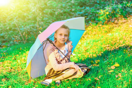 The girl is sitting on the green grass with a colored umbrella, closing from the suns rays and summer heat 写真素材