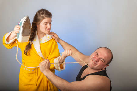 A wife in a yellow robe beats a bald husband, the concept of a family quarrel