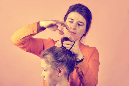 Young mother doing her babys hair on a pink background