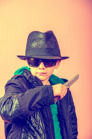A boy in a black hat, glasses and a jacket holds a knife near the throat, threatens with cold weapons