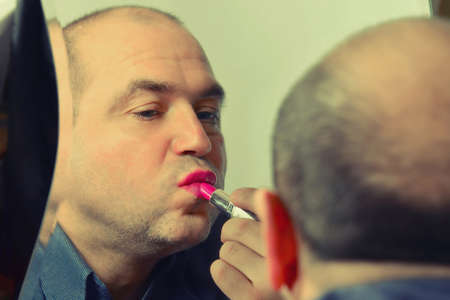 Adult man paints lips with red lipstick, fashion and style of a man with independent views, toned image close-up.