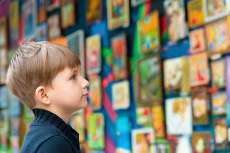 The boy looks at the paintings at the exhibition of pictorial art and creativity. Stok Fotoğraf