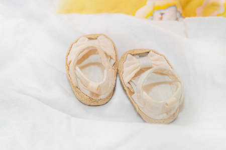 Shoes for a newborn baby on a white bedspread, booties for a child.