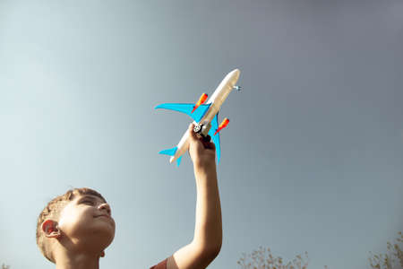 The boy is holding an airplane in his hand against the blue sky