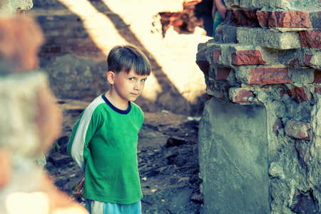 Poor and unhappy orphan boy, stands in a ruined building and looks out with danger. Staged photo. Stock Photo