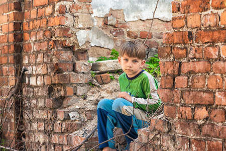 Poor and unhappy orphan boy, sitting on the ruins and ruins of a destroyed building. Staged photo.