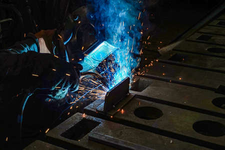 The working welder performs welding work in production using electric arc metal welding.